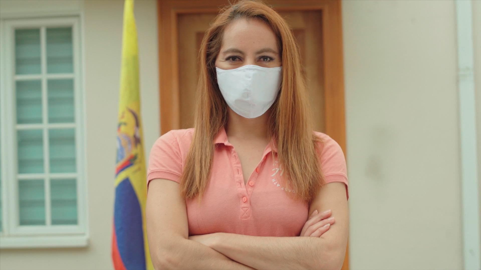 Imagen de mujer ecuatoriana con bandera en la parte posterior, usando mascarilla